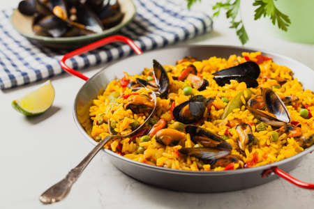Traditional paella with mussels. Front view. Stone white background.