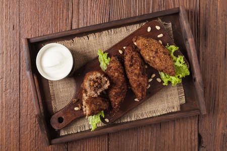 Traditional arabic kibbeh with lamb and pine nuts. Top view. Natural wooden background. Stock Photo