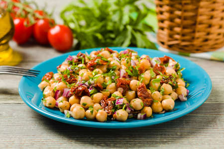 Chickpeas salad with onion and dried tomatoes. Front view. Stock Photo