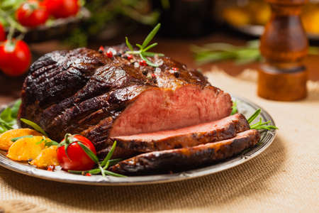 Roasted brisket. Rustic style, natural wooden background. Dark style. Front view. Stock Photo