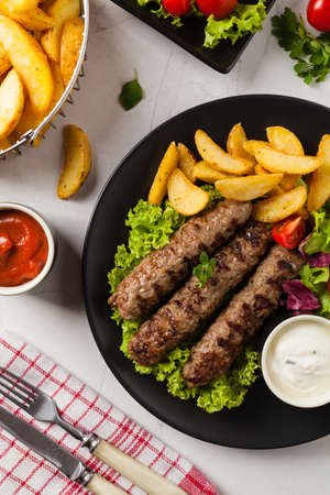 Traditional cevapcici served with baked potatoes. Flat lay. Stone background. Top view. Фото со стока
