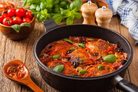 Pollo de elaboración tradicional en salsa de tomate cacciatore. Vista frontal.