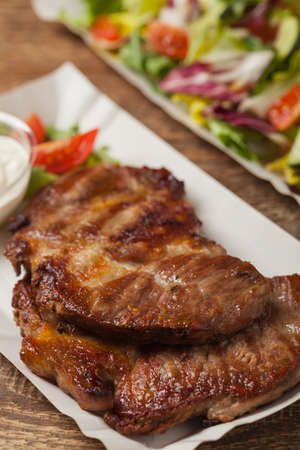 Set. Grilled pork neck served with French fries or bread and salad, served on paper trays. Front view.