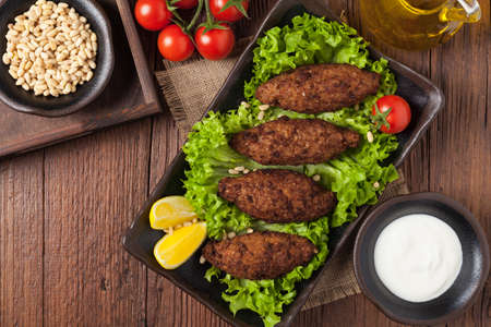 Traditional arabic kibbeh with lamb and pine nuts. Top view. Natural wooden background. Banco de Imagens