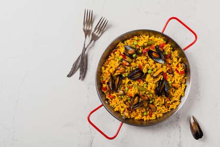 Traditionelle Paella mit Muscheln. Draufsicht. Steinweißer Hintergrund. Standard-Bild