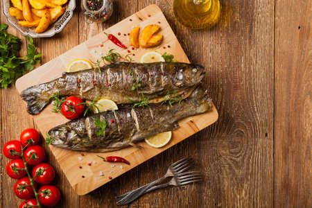 Grilled whole trout. Served with baked potatoes. Top view.