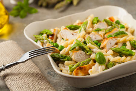 Italian pasta fusilli. Salad with chicken and asparagus in Béchamel sauce. Best eaten hot. Stone background. Front view. Stockfoto