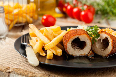 Chicken Kiev (de Volaille chop) with french fries and salads. Front view.