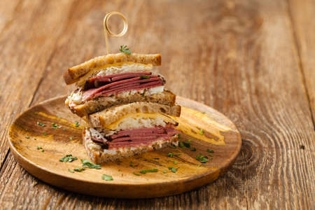 Reuben sandwich. New York sandwich with pastrami, thousand island sauce and sauerkraut. Front view. Fast food.