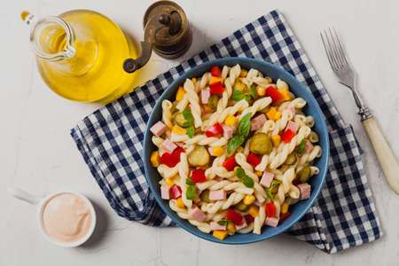 Italian fusilli pasta in a salad with ham and vegetables. Top view. Background white stone Banco de Imagens
