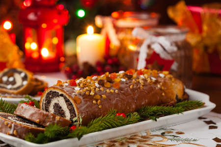 Poppy seed roulade in Christmas decoration. Served with coffee or tea. Front view.