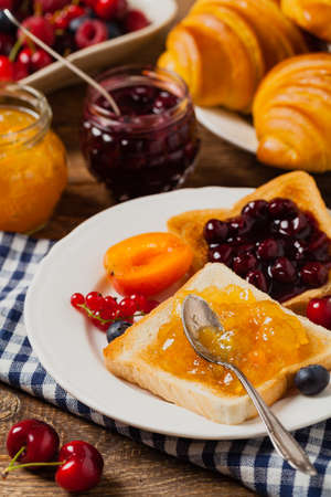 Breakfast. Toasts with cherry or peach jam and fresh fruit. Front view.