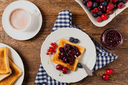 Breakfast. Toasts with cherry or peach jam and fresh fruit. Top view. Flat lay.