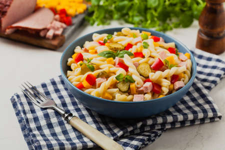 Italian fusilli pasta in a salad with ham and vegetables. Front view. Background white stone
