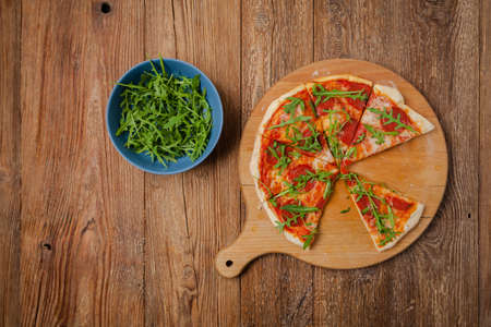 Ready to eat Pizza pepperoni on a wooden board with rucola. Top view. Concept. Imagens