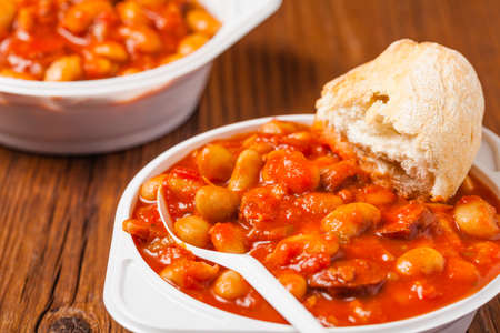 Baked beans in tomato sauce served in plastic cups. Front view. Imagens