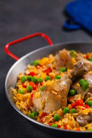 Arroz con pollo. Baked pieces of chicken with bone, rice with paprika and peas.