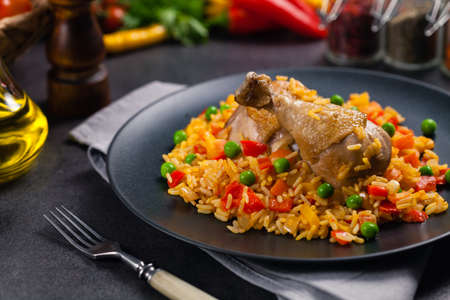 Arroz con pollo. Baked pieces of chicken with bone, rice with paprika and peas