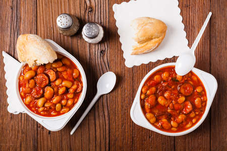 Baked beans in tomato sauce served in plastic cups. Top view.