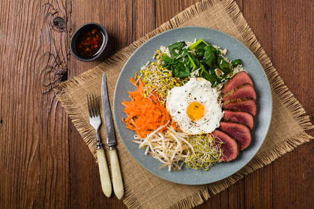 Korean beef with sprouts, spinach and fried egg. Top view. Imagens