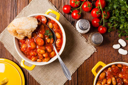 Baked beans in tomato sauce served in yellow, clay bowls. Top view.