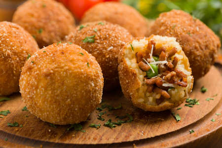 Classic, Italian arancini. Rice balls with minced meat. Front view. Close up.