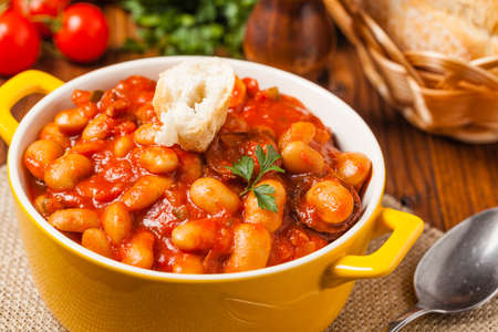Baked beans in tomato sauce served in yellow, clay bowls. Front view. Imagens