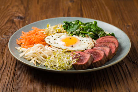 Korean beef with sprouts, spinach and fried egg. Front view.