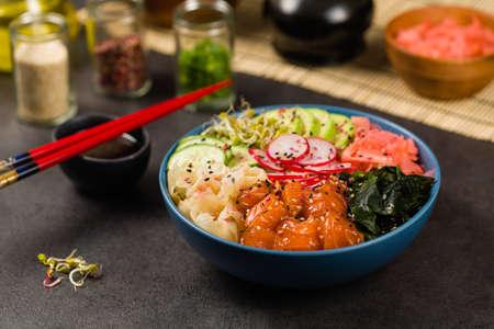 Hawaiian salmon poke bowl with seaweed, avocado, sesame seeds. Imagens