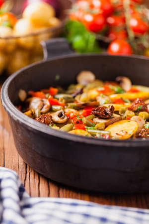 Fried pan vegetables, with mushrooms and dried tomatoes. Seasoned with a mix of herbs.Top view.