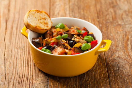 Traditional Italian caponata, served with croutons in a yellow, sunny pot. Decorated with basil and pine nuts. Front view. Stock Photo
