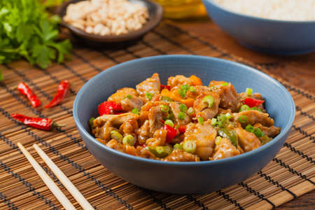 Chicken kung pao. Fried chicken pieces with peanuts and peppers. Front view. Stok Fotoğraf