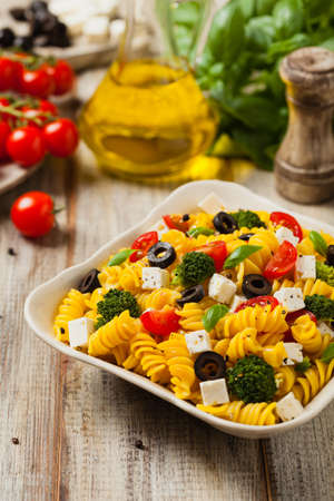 Salad with pasta and feta cheese. Front view.