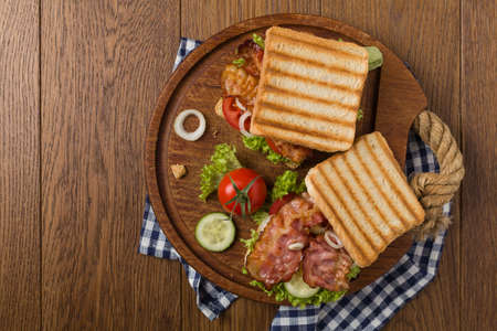 Toasted sandwich with bacon, tomato, cucumber and lettuce. Top view.