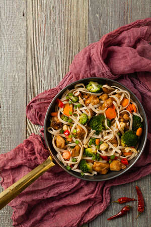 stir-fry pasta with chicken, broccoli and carrots. Top view. Gray wooden background. Served in a frying pan. Stok Fotoğraf