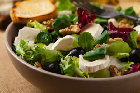 Italian spring salad with goat cheese, grapes and walnuts. Served with croutons. Stok Fotoğraf