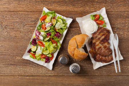 Set. Grilled pork neck served with French fries or bread and salad, served on paper trays.Top view.