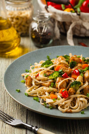 stir-fry pasta with chicken, broccoli and carrots. Served on a gray plate. Stok Fotoğraf