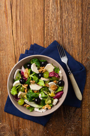 Italian spring salad with goat cheese, grapes and walnuts. Served with croutons. Top view.