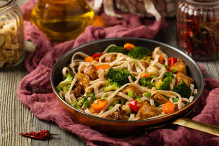 stir-fry pasta with chicken, broccoli and carrots. Served in a frying pan.