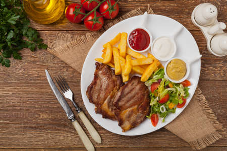 Grilled pork neck served with French fries and salad. Top view.