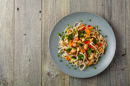 stir-fry pasta with chicken, broccoli and carrots. Top view. Gray wooden background. Served on a gray plate. 写真素材