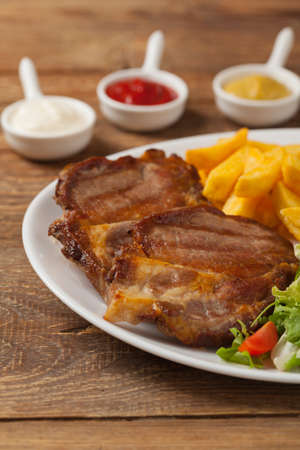 Grilled pork neck served with French fries and salad. Front view.