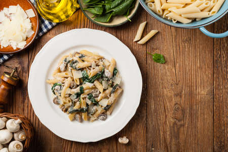 Penne pasta with spinach and mushrooms. Sprinkled with cheese. Top view. Stock Photo