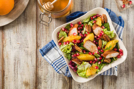 Spring salad with chicken, pomegranate, orange, pecan nuts and honey. Old table background. Top view. Wooden table background.