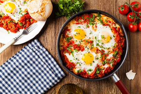 Shakshouka, dish of eggs poached in a sauce of tomatoes, chili peppers, onions. Top view. 免版税图像
