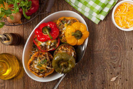 Colorful baked with cheese, stuffed peppers with rice and minced meat. Top view. Imagens