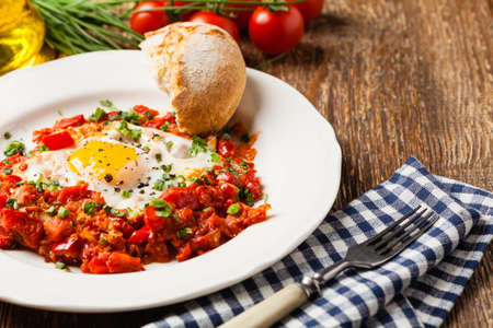 Shakshouka, dish of eggs poached in a sauce of tomatoes, chili peppers, onions. Front view.