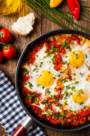 Shakshouka, dish of eggs poached in a sauce of tomatoes, chili peppers, onions. Top view. Imagens