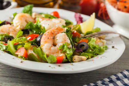 Shrimp salad with tomato, olives and cashew nuts. Front view. Imagens